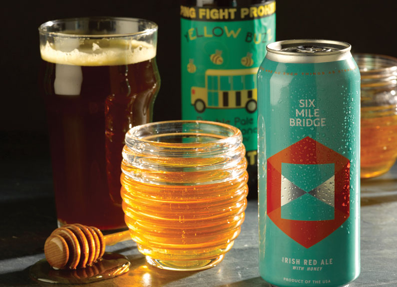 a can of beer, a bottle of beer, a glass of honey with a dipper and a glass of beer