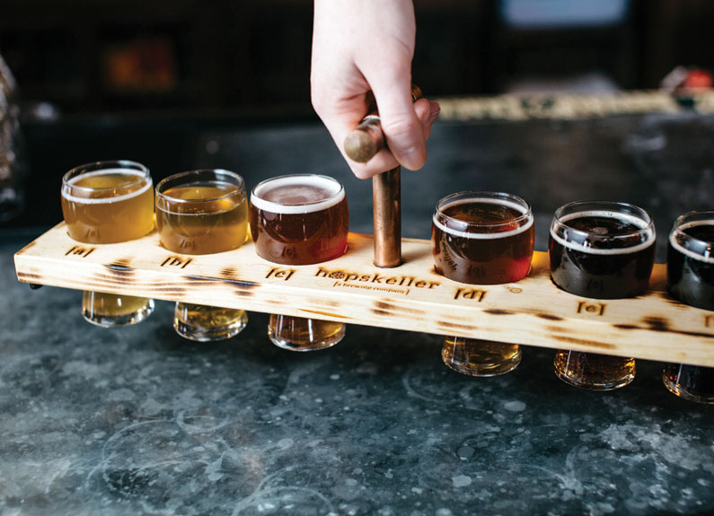 a flight of beers with the hopskeller logo on the board