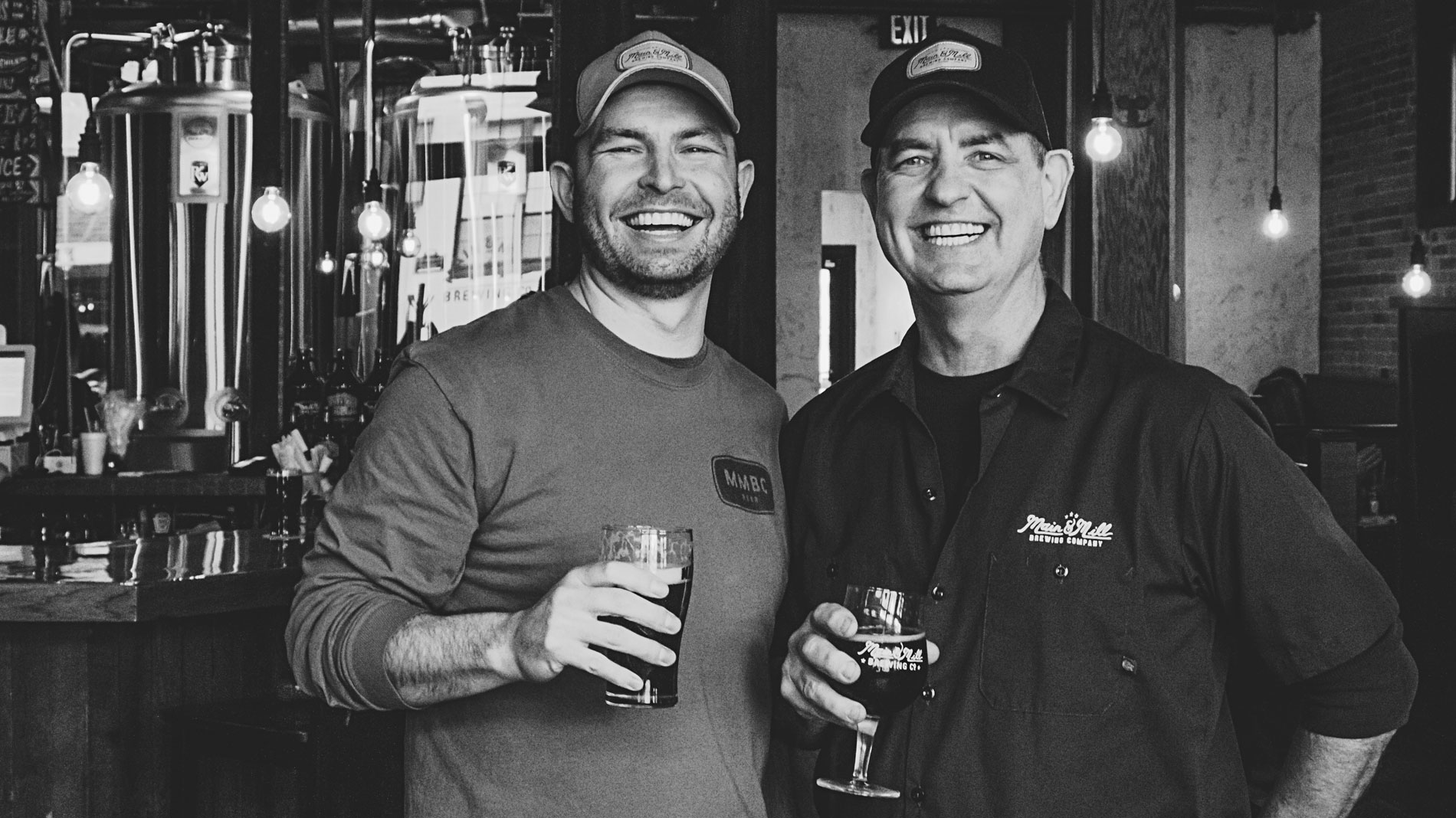 two smiling menin baseball caps holding beers and standing in front of brewing equipment