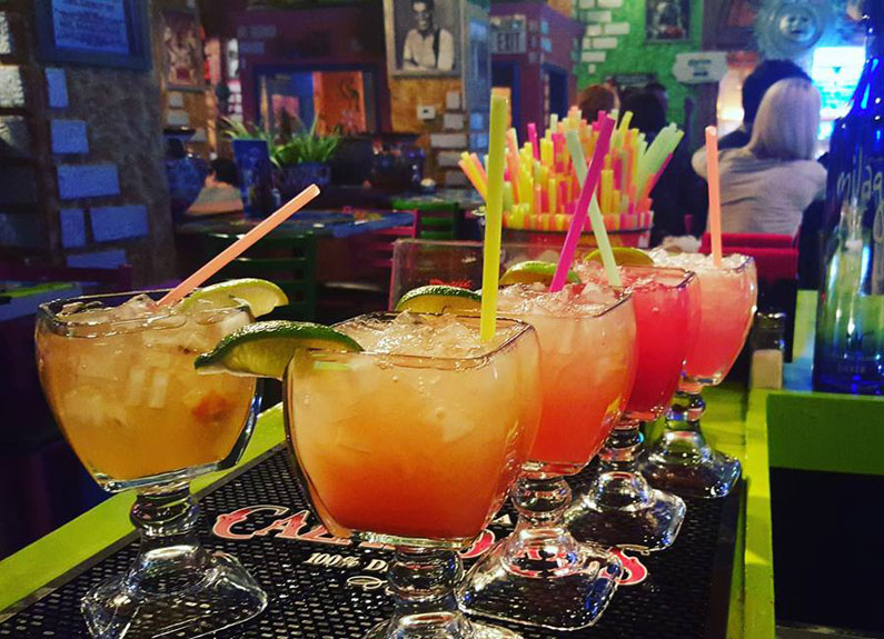 a row of margaritas in glasses on a bar with colorful straws