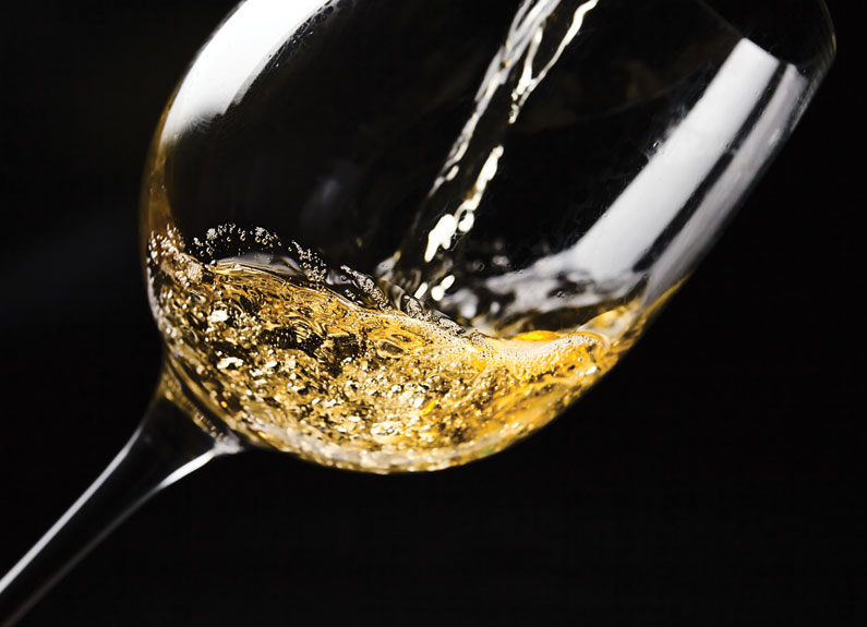 a close up shot of white wine in a glass at a angle