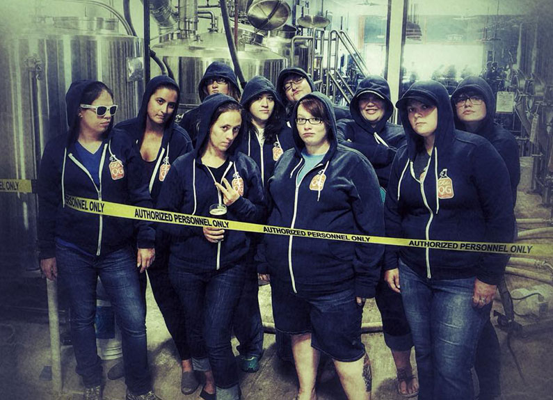 a group of women in hoodies holding beer