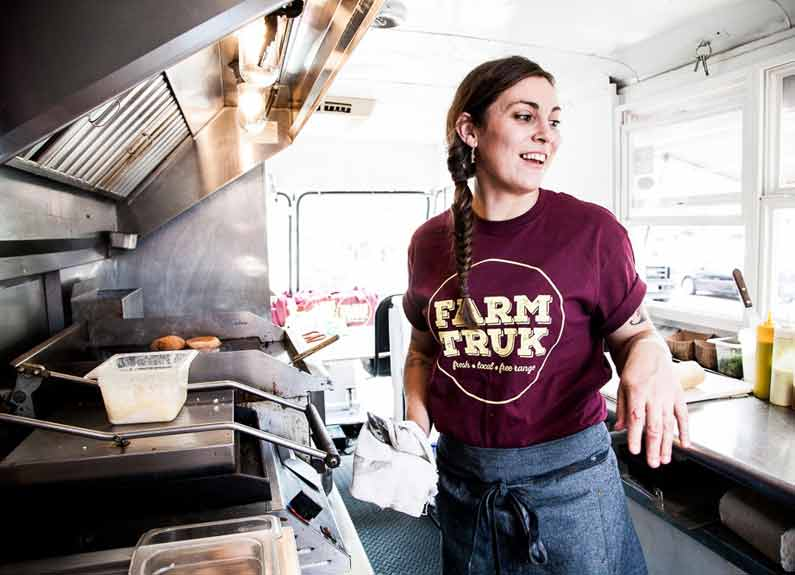a smiling woman with a farmtruk tshirt working in a food truck