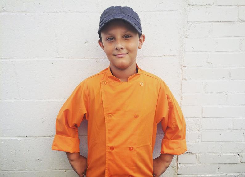 a boy wearing a baseball cap and orange chef's coat
