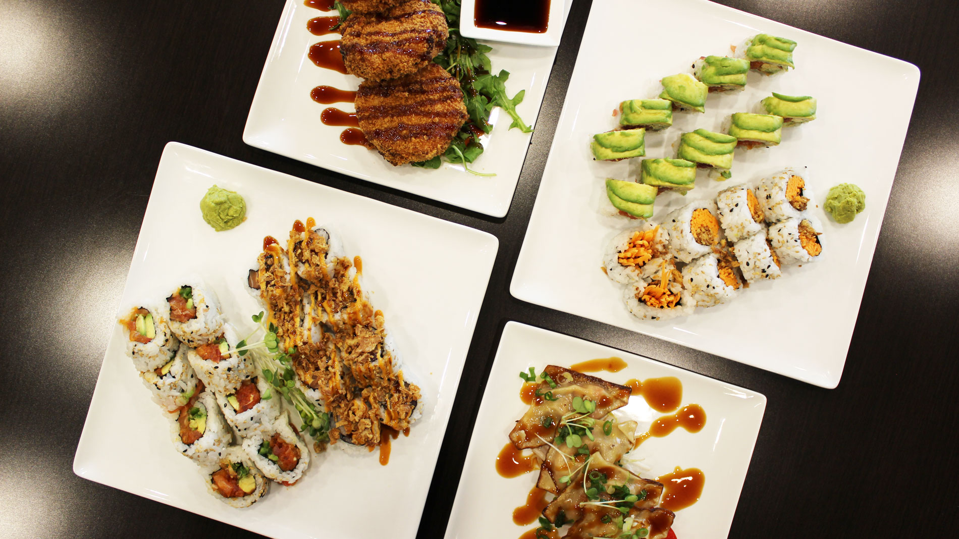 four square white plates holding sushi rolls and appetizers