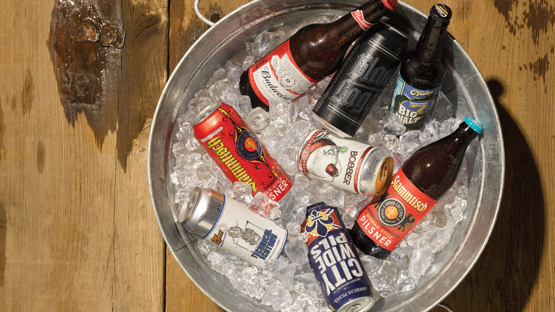 several bottled and canned lagers in a bucket of ice