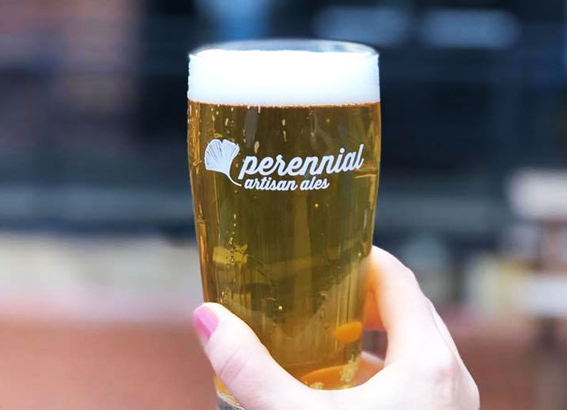 a hand holding a glass of pale beer that says perennial artisan ales