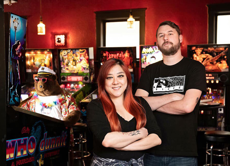 a man and a woman standing in front of a wall of pinball machines with their arms crossed