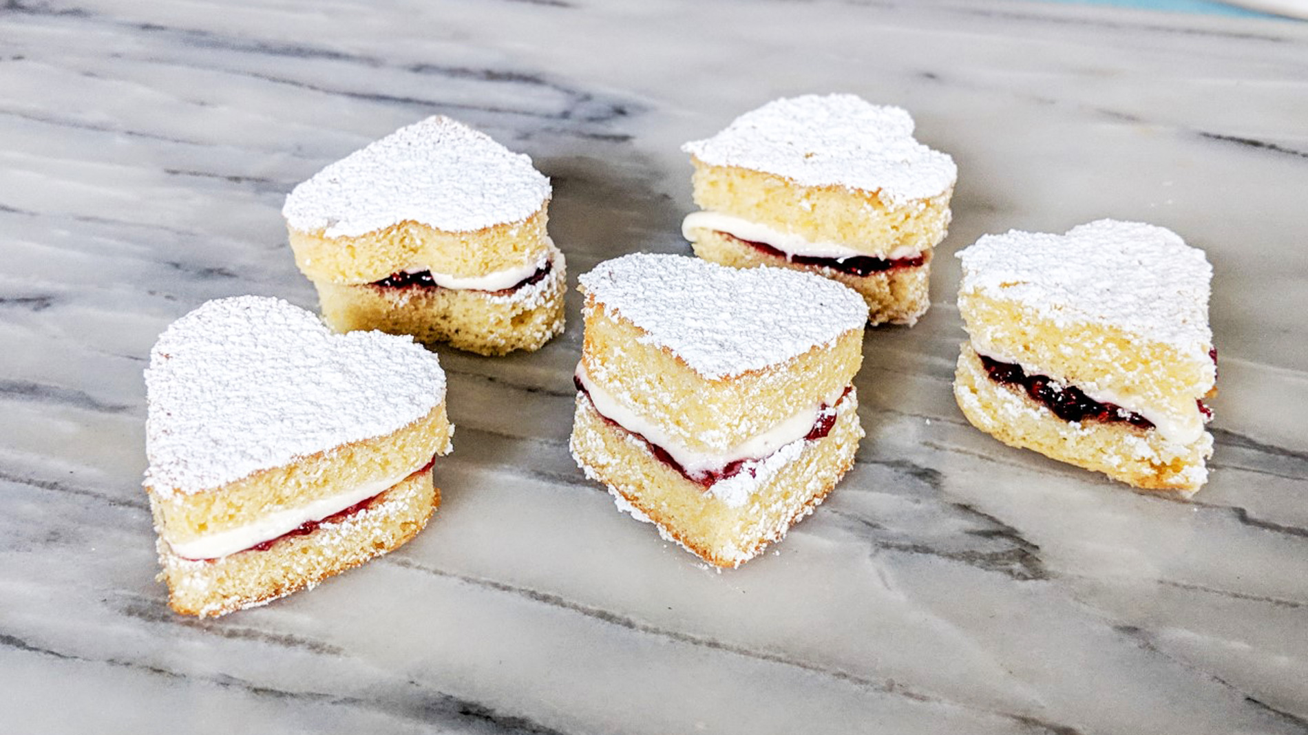 a stack of heart-shaped victoria sponge cakes on a marble counter