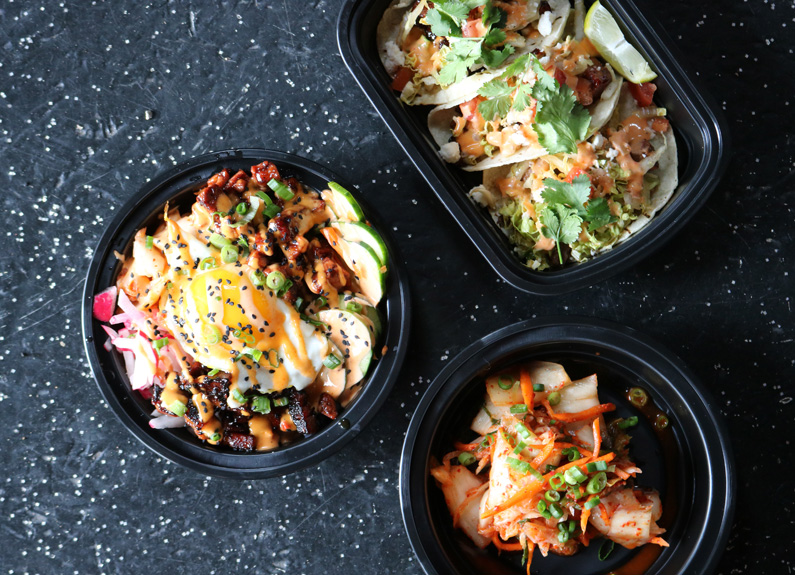 three korean dishes in black bowls on a black countertop