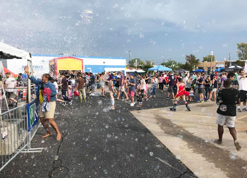 a crowd of people at a street festival with a bubble machine