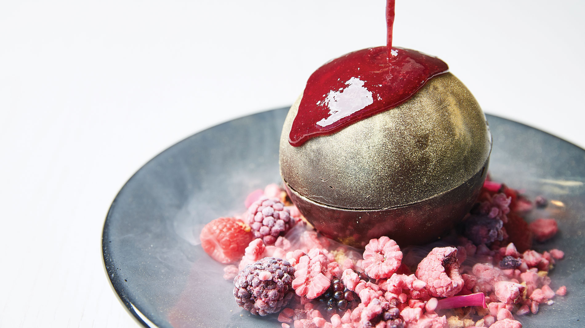 a dessert consisting of a chocolate orb atop freeze-dried berries being drizzled with berry sauce
