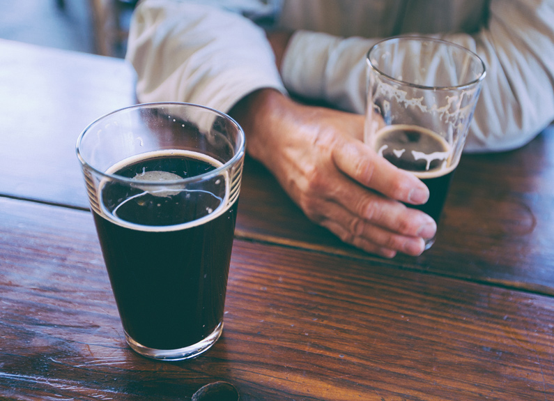 two dark stout in beer pint glass on a bar with one hand holding the glass