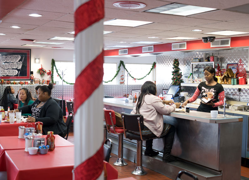 the interior of a diner with people sitting at the counter interacting with the staff