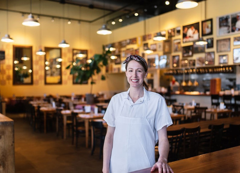 a woman in chef whites standing in front of a dining room