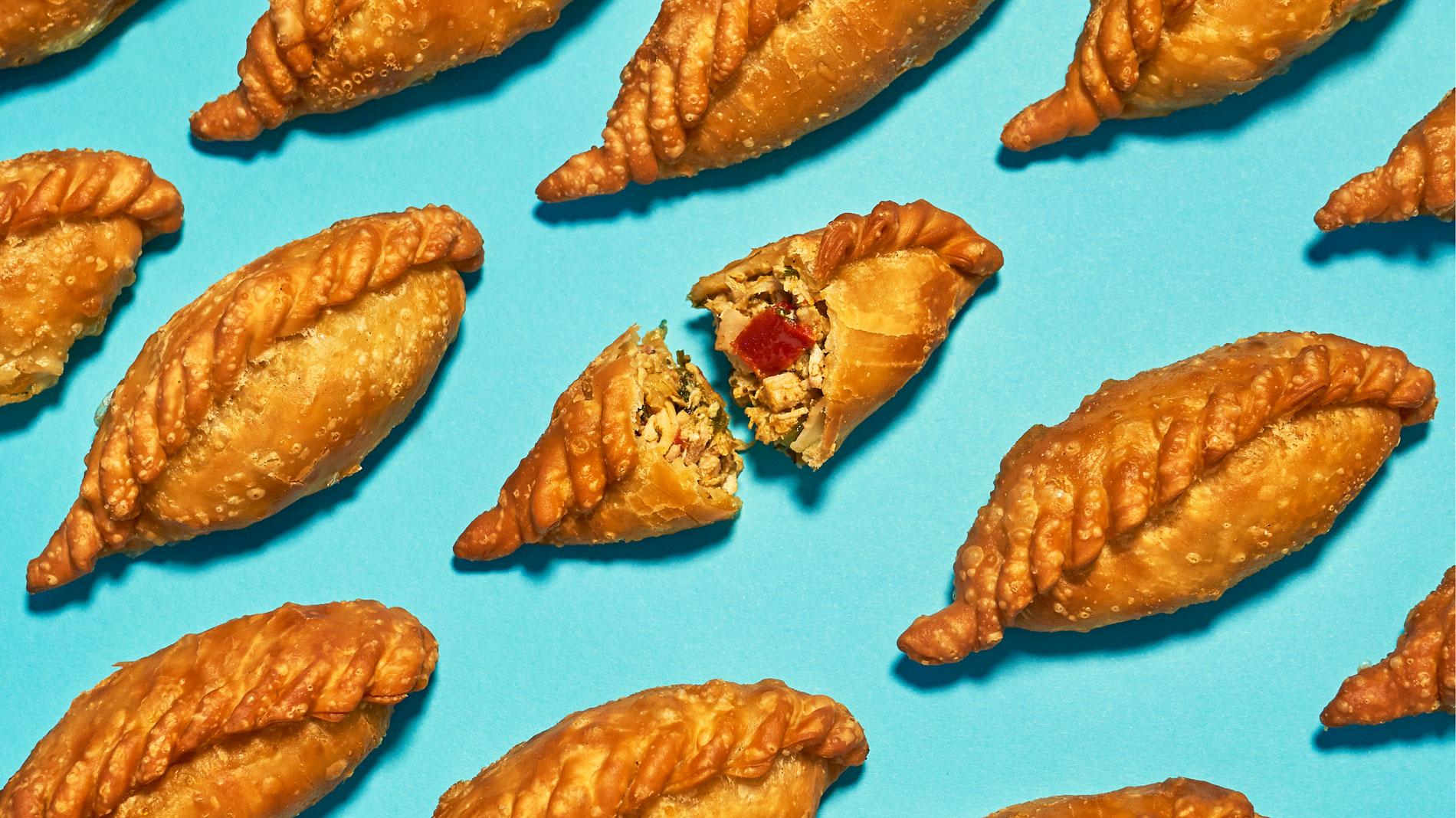 several empanadas lined up diagonally on a blue background