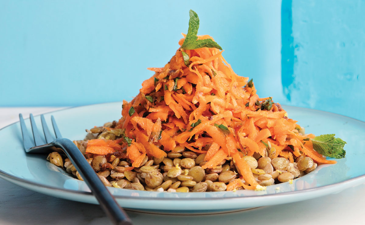 a plate of lentils topped with shredded carrots