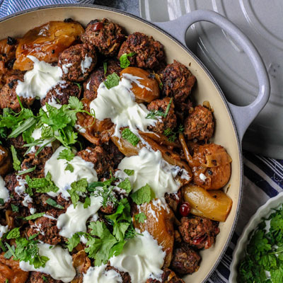 a pan of moroccan meatballs with herbed yogurt