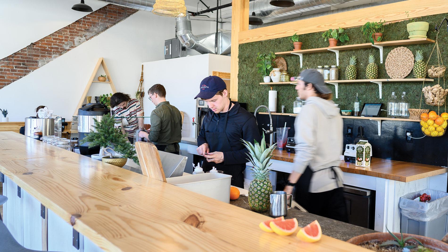 three men working behind a light wood juice bar