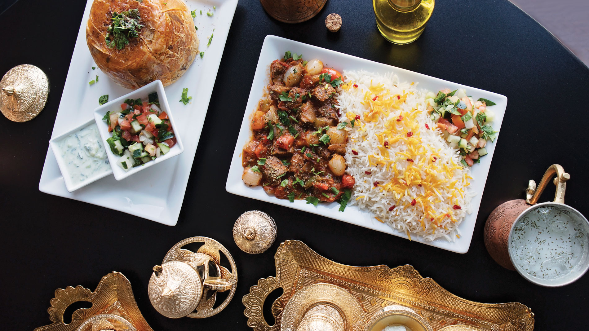 middle eastern dishes and a brass turkish coffee service on a table with a black table cloth
