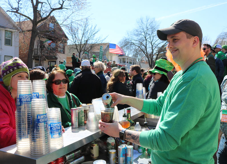 a man in a green sweatshirt pouring beer outside on st. patrick's day