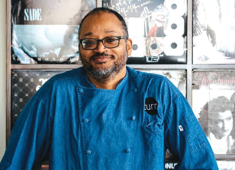 a smiling chef behind a turntable and a record wall
