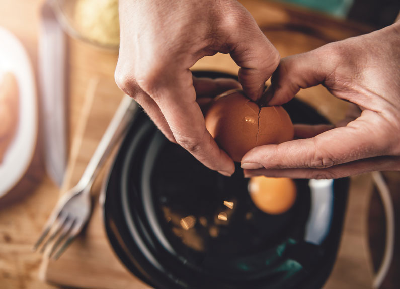 two hands cracking a brown egg into a frying pan