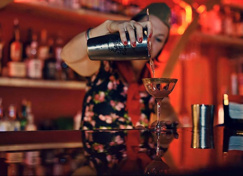 a cocktail glass in the foreground obscuring a bartender pouring the drink into the glass from a shaker