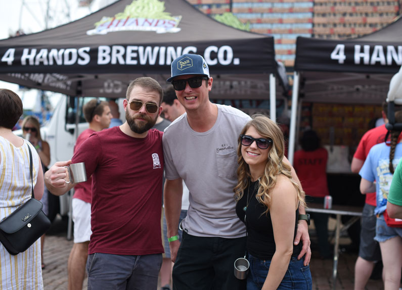 three people at an outdoor beer festival