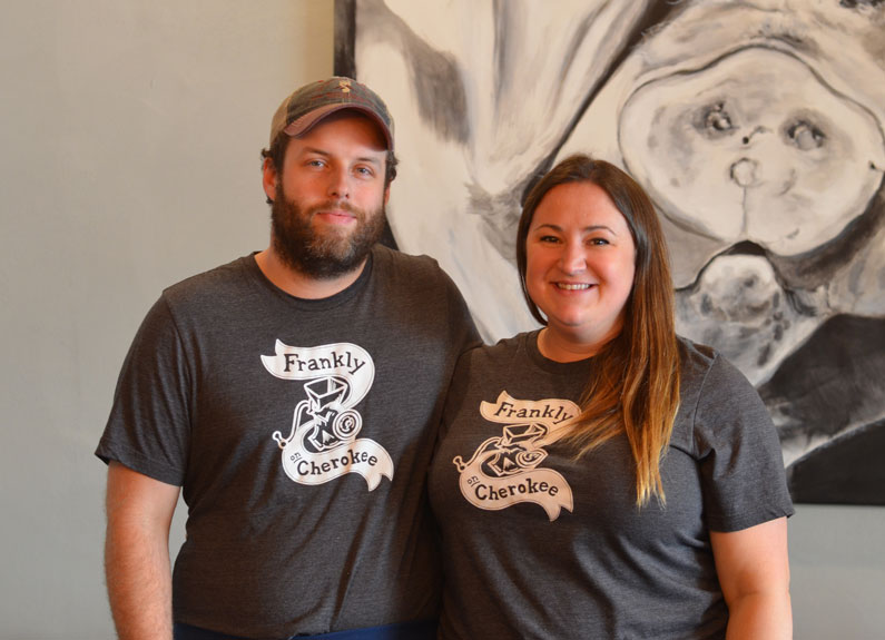 a man and women in gray frankly sausages tshirts in front of a large picture of a pig