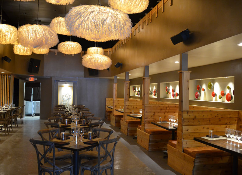 a restaurant dining room with large white light fixtures