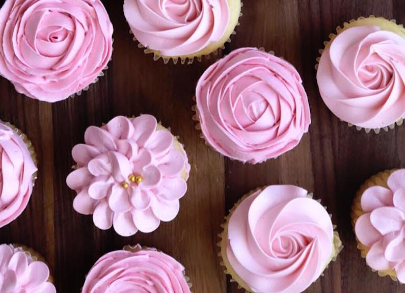 several pink frosted cupcakes in lines