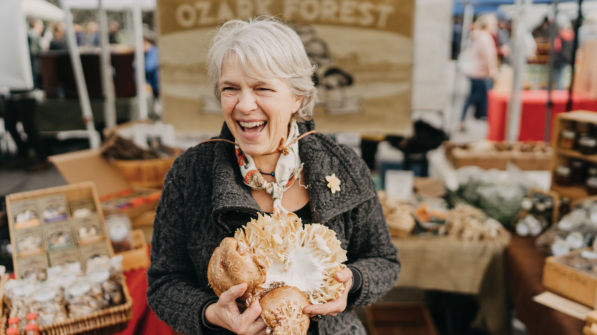 a laughing woman with a very large shiitake mushroom