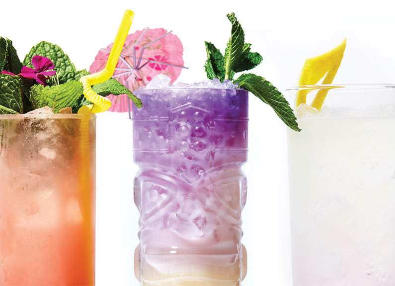 three brightly colored cocktails garnished with mint, umbrellas and straws