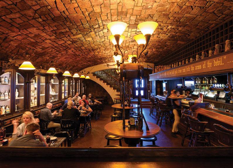 a dimly lit tavern wtih a brick barrel ceiling
