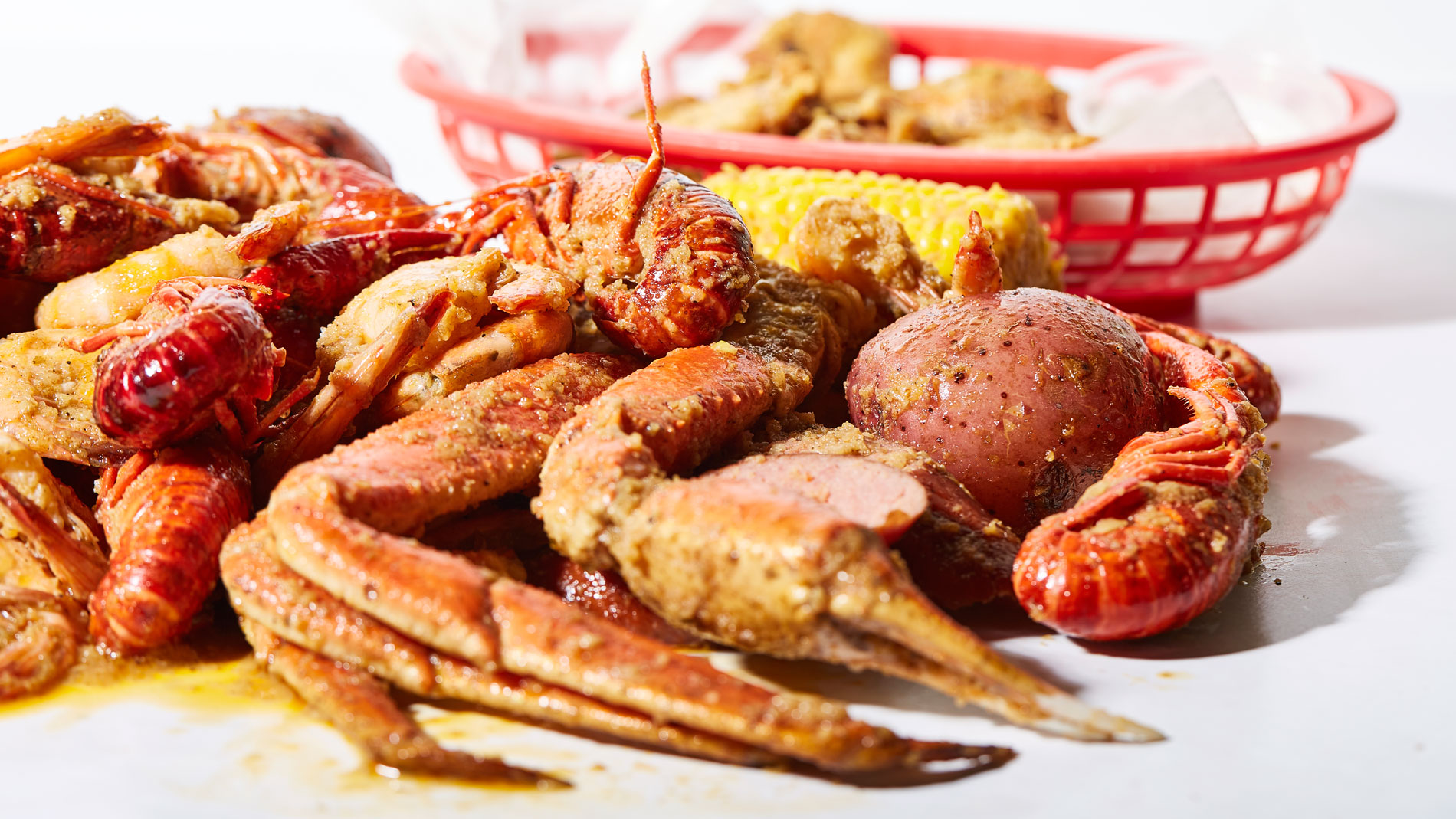 a pile of red crawfish, corn and sausages