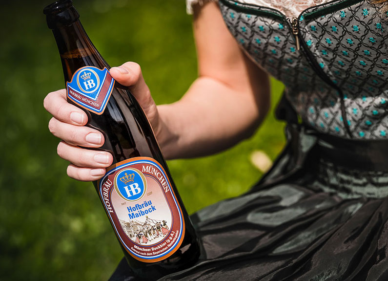 a woman's hand holding a bottle of hofbrau maibock