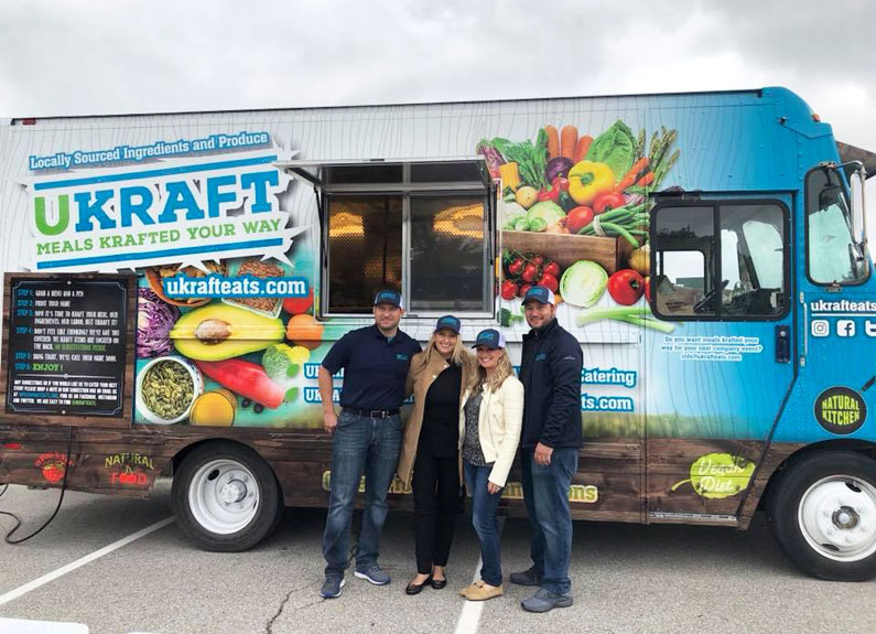 people standing in front of a blue food truck