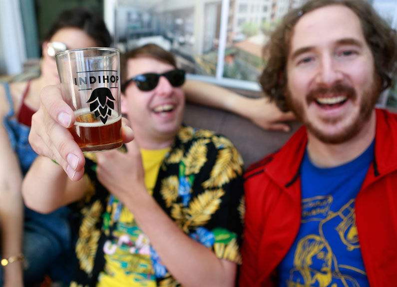 two men at a beer festival holding a tasting glass that says indihop