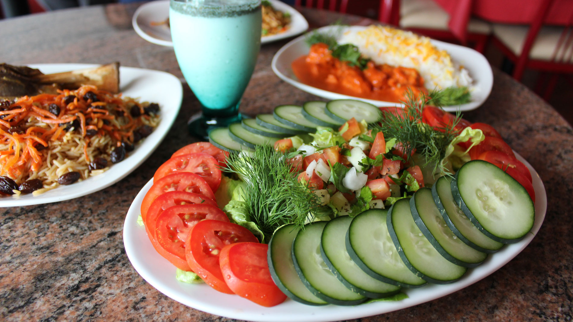 a cucumber and tomato salad on a table with other middle eastern dishes in the background