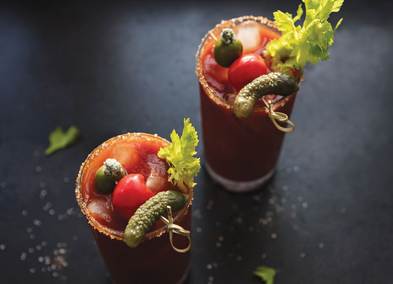 two bloody marys with pickles, tomatoes and salt rims for garnish