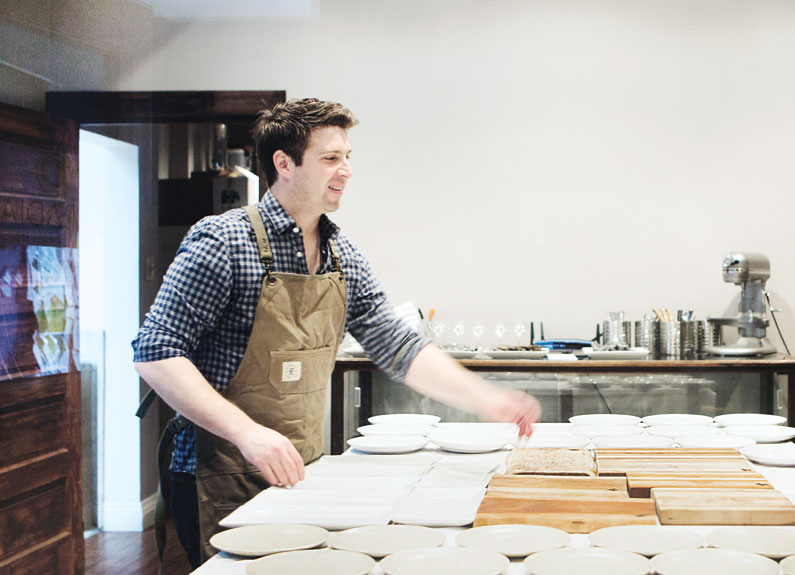a chef in a ginghan shirt and khaki apron working at a large white counter