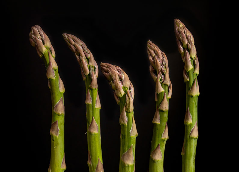 five green asparagus tips on a black background