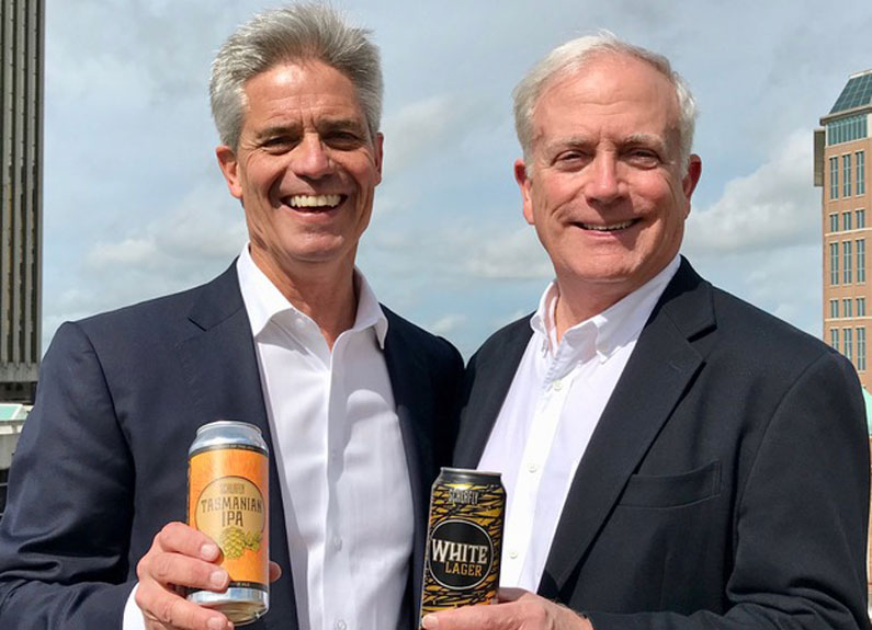 two men in black suitcoats holding cans of beer