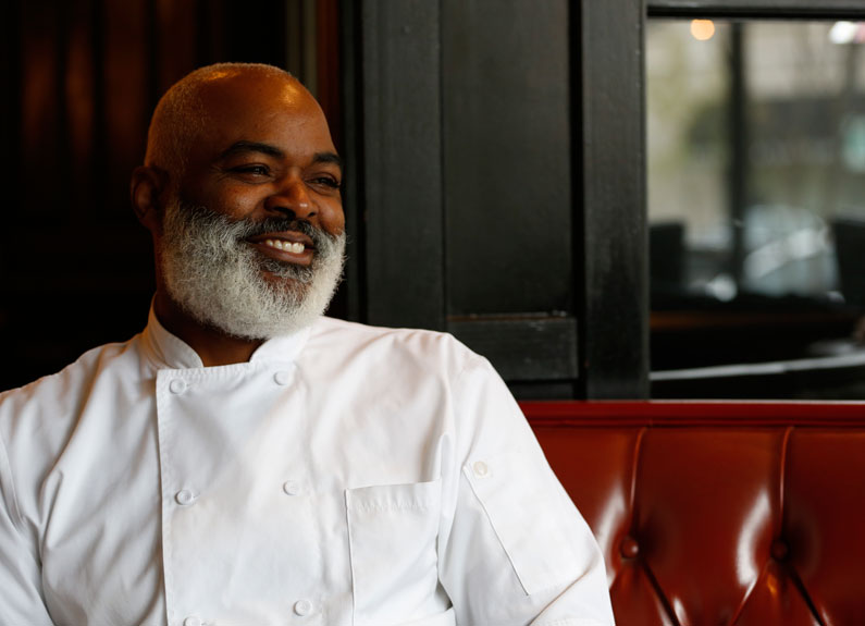 a smiling chef with a gray beard in a chef coat sitting in a restaurant banquette