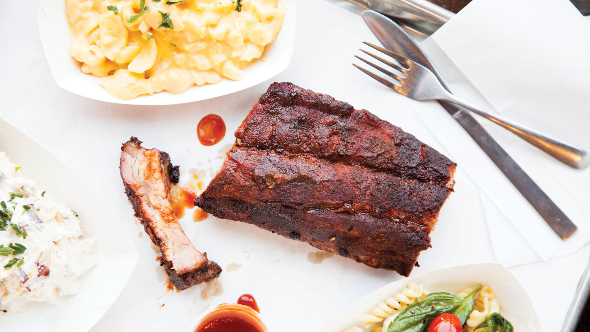 three barbecue ribs with sides of mac and cheese and salad on a white tablecloth