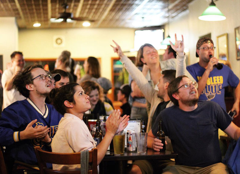 a crowd of st louis blues fans watching a hockey game in a bar