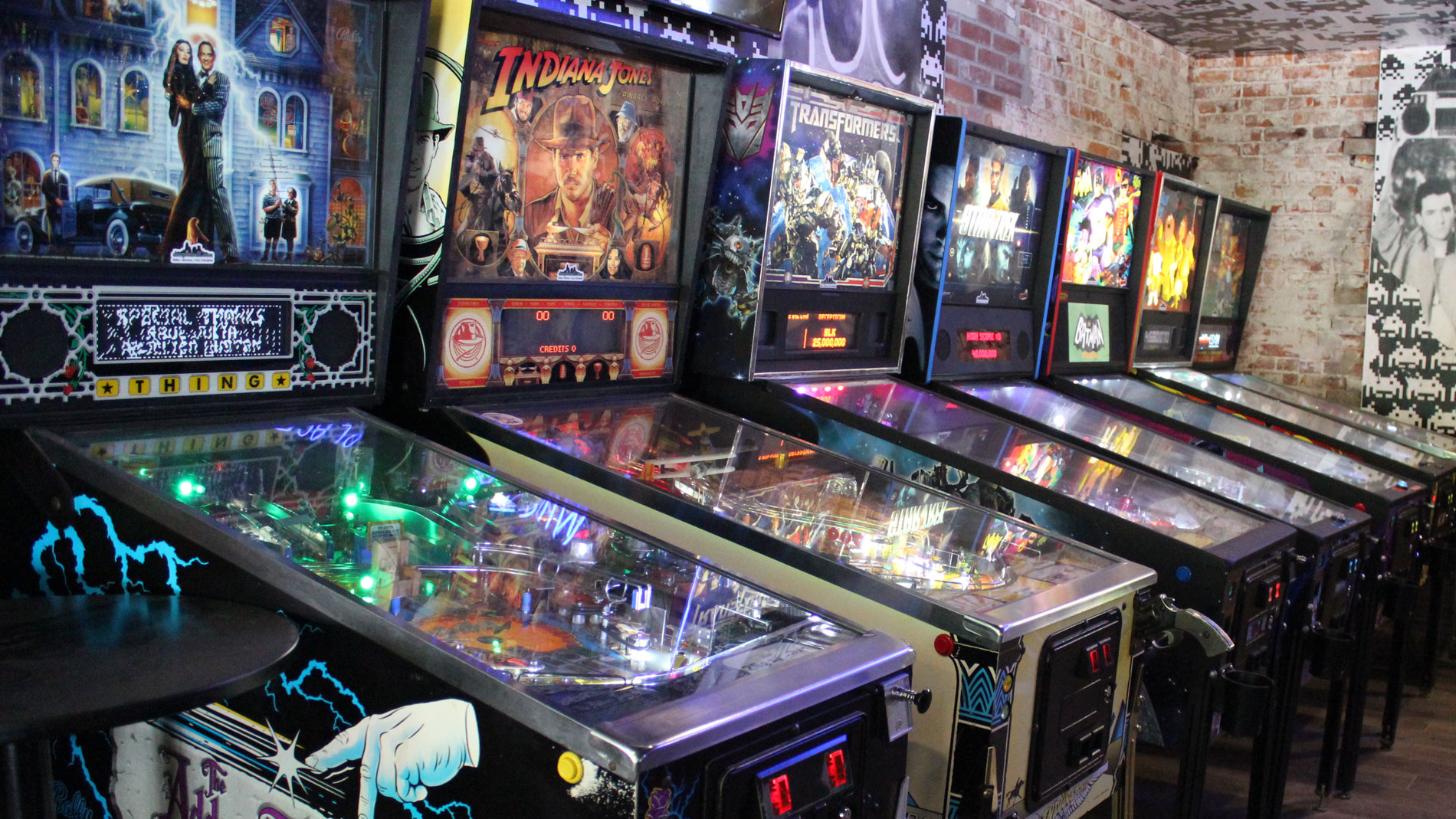 a row of pinball machines at a bar