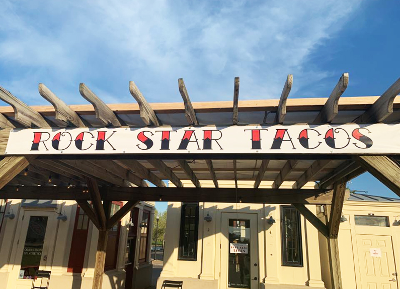 a wooden pergola with the words rock star taco painted on it
