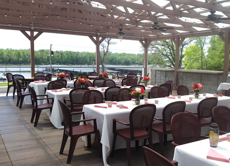 several large set tables with white tablecloths under a pergola